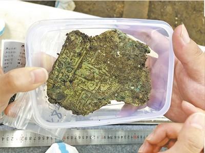 8号坑出土的青铜容器残片,纹饰精美繁复。