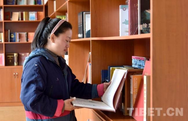 图为尼玛仓拉正在翻看书籍 摄影:王媛媛