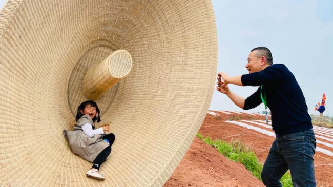 开幕式现场,焦兴涛在自己的作品前为村里的孩子拍照