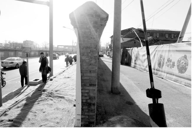 墙隔开新大街和老胡同:左为前门大街,右为铺陈市胡同。