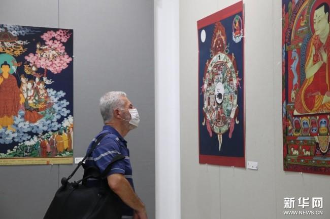 8月25日,一名观众在马耳他首都瓦莱塔欣赏唐卡作品。新华社记者 陈文仙 摄