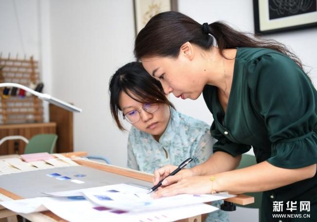 在广州荔湾区泮塘五约的法绣工坊,王颖峰(右)给学员讲授法绣针法(8月25日摄)。