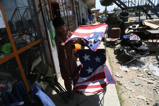 7月3日,在阿富汗帕尔万省的巴格拉姆空军基地附近,当地居民在美军遗留下的物品中回收废旧物。新华社发(拉赫马图拉·阿里扎达摄)