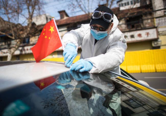 """2月29日,""""W大武汉紧急救援队""""队员朱伟将国旗插在车上。疫情期间,由志愿者组成的""""W大武汉紧急救援队""""接送缺乏交通工具去医院的待产孕妇,成为即将出生的新生命的""""摆渡人""""。新华社记者 肖艺九 摄"""