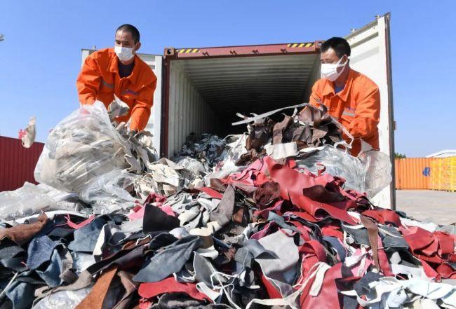 ▲2020年12月21日,工人在厦门海关的海沧查验场清理查获的进口牛皮革洋垃圾。(新华社)